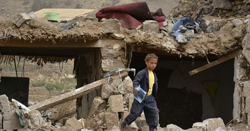 Yemen children walking on ruins